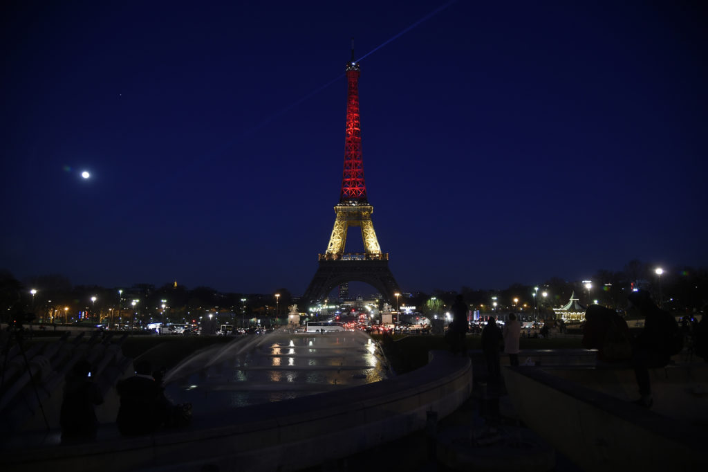 A picture taken on March 22, 2016 shows the Eiffel Tower in Paris illuminated in colours of the Belgian flag in tribute to the victims of terrorist attacks in Brussels. Around 35 people were killed and more than 200 wounded in a series of attacks in Brussels today claimed by the Islamic State group and described as a strike at the very heart of Europe.  AFP PHOTO / LIONEL BONAVENTURE / AFP / LIONEL BONAVENTURE        (Photo credit should read LIONEL BONAVENTURE/AFP/Getty Images)