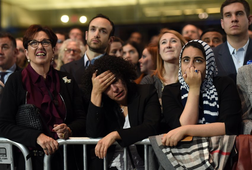 TOPSHOT - People watch elections returns during election night at the Jacob K. Javits Convention Center in New York on November 8, 2016. US Democratic presidential nominee Hillary Clinton will hold her election night event at the convention center. / AFP PHOTO / DON EMMERT