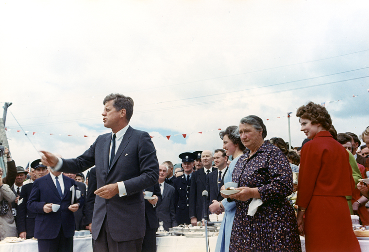 ST-C232-1-63 27 June 1963 President Kennedy's trip to Ireland. The President greets relatives at a tea held at the home of Mrs. Mary Ryan, the President's second cousin, in Dunganstown, Ireland, the President's ancestral homestead. President Kennedy, Mrs. Mary Ryan (flowered dress), Mrs. Josie Ryan (light blue dress), guests, others. Photograph by Cecil Stoughton, White House, in the John F. Kennedy Presidential Library and Museum, Boston.