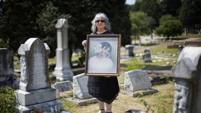 "In this Monday, Aug. 3, 2015 photo, Mary Phagan Kean holds a portrait of her great aunt, Mary Phagan as she poses for photo next to her grave, left, in Marietta, Ga. ""She's my family. She's my history. History is what makes you who you are,"" she says. Phagan Kean was 13, herself, when a teacher asked if she was related to the girl murdered at the National Pencil Co in 1913. (AP Photo/David Goldman)"