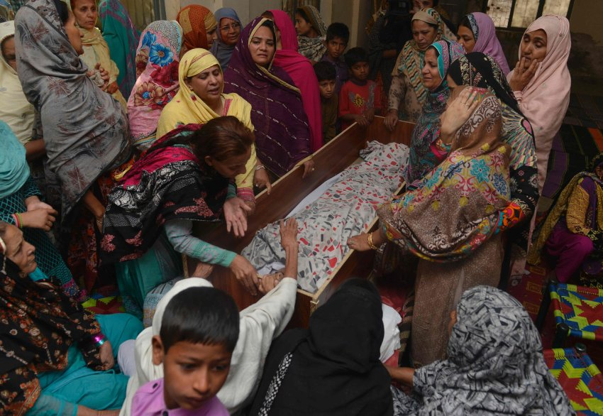 "Pakistani relatives mourn over the body of a victim during a funeral following an overnight suicide bombing in Lahore on March 28, 2016. The toll from a suicide blast in Pakistan's Lahore rose to 69, officials said on March 28, as authorities hunted for the ""savage inhumans"" behind the attack in a park packed with Christian families celebrating Easter Sunday. More than 200 people were injured, many of them children, when explosives packed with ball bearings ripped through crowds near a children's play area in the park in Lahore, leaving dozens dead or bloodied. / AFP PHOTO / ARIF ALI"