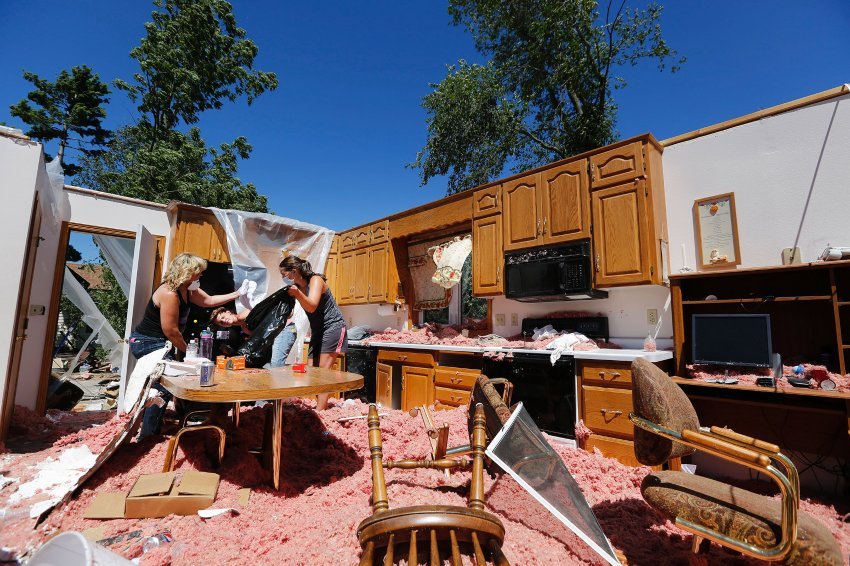 "Family members clean out the refrigerator of the home of Kathleen ""Tootz"" Tschumperlin, whose  home was destroyed after a tornado tore through Watkins the evening before, Tuesday, July 12, 2016 in Watkins, Minn.. From left is Linda Linz, the daughter of Tschumperlin, Linz's daughter-in-law Michelle Linz and daughter Hannah Hiltner. (Leila Navidi/Star Tribune via AP)"