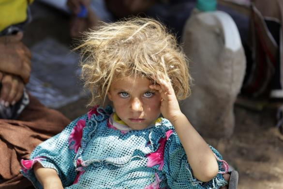 A girl from the minority Yazidi sect, fleeing the violence in the Iraqi town of Sinjar, rests at the Iraqi-Syrian border crossing in Fishkhabour, Dohuk province, Iraq, August 13, 2014. REUTERS/Youssef Boudlal